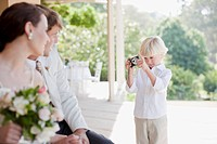 Boy taking picture of bride and groom