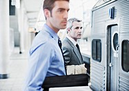 Businessmen waiting for train in train station