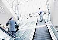 Businessman descending escalator