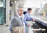 Businessmen waiting for train on platform