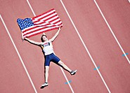 Runner laying on track with American flag