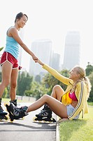 Woman on rollerblades helping friend up from ground