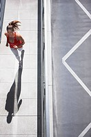 Woman running on urban sidewalk