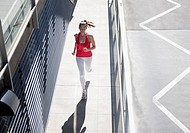 Woman running on urban sidewalk (thumbnail)