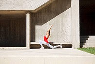Woman stretching near concrete bench