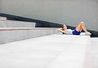 Woman doing sit_ups on urban stairs