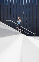 Woman running up urban staircase
