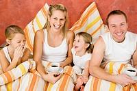 Mama, Papa und Kind frühstücken im Bett