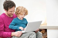 Close_up of a man assisting his son in using a laptop