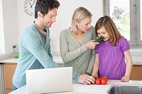 Family cooking with the recipe on a laptop