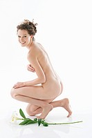 Naked woman kneeling beside a flower and smiling