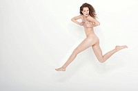Naked woman covering her breasts and jumping (thumbnail)