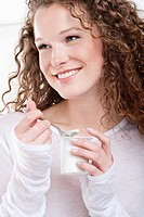 Close_up of a woman eating yogurt