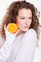 Close_up of a woman holding a half of an orange