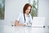 Female doctor sitting in an office inserting CD into a laptop