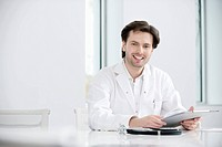 Male doctor holding a medical report and smiling