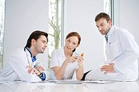 Three doctors examining medicine
