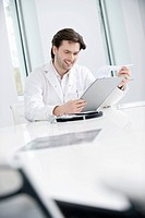 Male doctor examining a medical report and smiling