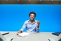Businessman doing paperwork and smiling in a conference room