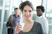 Businesswoman holding a disposable cup with colleagues in the background