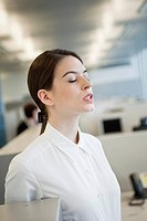 Businesswoman standing with her eyes closed in an office
