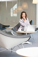 Businesswoman waiting in an office and using a laptop