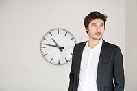 Businessman standing in front of a clock