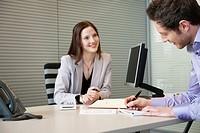 Man signing documents with a female real estate agent sitting in front of him (thumbnail)