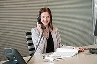 Businesswoman talking on a telephone in an office