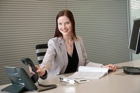 Businesswoman holding a telephone receiver in an office