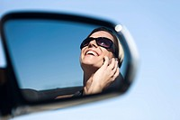 Woman talking on cell phone, reflection in side_view mirror