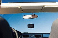 Woman driving car, reflection in rearview mirror