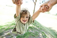 Boy being swung through air by his arms