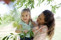 Mother holding young daughter outdoors, girl holding onto tree branch