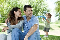 Couple relaxing together outdoors, woman looking over shoulder at son playing in background