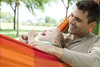 Father and daughter relaxing together in hammock, both laughing