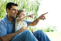 Father holding young daughter on lap outdoors, both pointing and looking away