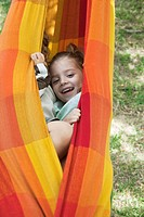Children hiding together in hammock (thumbnail)