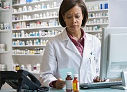 African American pharmacist filling prescription