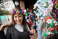 Mixed race woman trying on headdress at souvenir shop