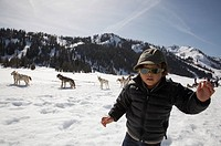 Mixed race boy in snow with dogs and dogsled