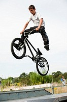 Teenage boy doing trail bike aerial stunts in a skate park, Aberystwyth Wales, UK