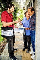Carrying his official shoulder bag, a 2010 U.S. Census enumerator shows his ID card while interviewing a Hispanic married couple in Southern Californi...