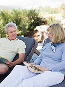 Mature couple relaxing on loungers with books