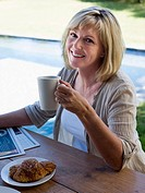 Woman outdoors with coffee and breakfast