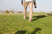 Man walking in field with video camera