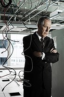Businessman in office with cables hanging from ceiling