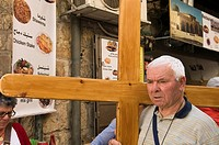 a pilgrim carries the cross following Jesus' steps on the Via Dolorosa in Jerusalem