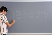 Male high school student writing lines on blackboard