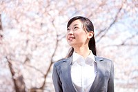 Businesswoman standing under cherry blossoms